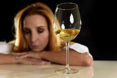Betrunkene alkoholische blonde Frau allein in vergeudetem deprimiertem trinkendem leidendem Kater des Weißweinglases Stockfotografie