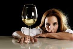 Betrunkene alkoholische blonde Frau allein in vergeudetem deprimiertem trinkendem leidendem Kater des Weißweinglases Stockfoto