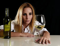 Betrunkene alkoholische blonde Frau im vergeudeten deprimierten Gesicht, das zum Weißweinglas durchdacht schaut Stockbild