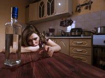 Betrunkene deprimierende Frau betrachtet die Flasche mit Alkohol Stockbild