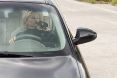 Betrunkene fahrende und trinkende Frau Lizenzfreie Stockfotos