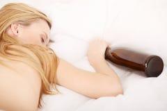 Betrunkene Frau, die auf Bett schläft Lizenzfreies Stockbild