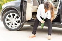Betrunkene Frau, die in der Tür ihres Autos sitzt Stockbild