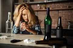 Betrunkene junge Frau, die deprimiert ist Stockfotos