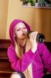 Betrunkene junge Frau mit Flasche Alkohol Stockfotografie