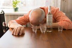 Betrunkene kahle ältere Personen, die auf dem Tisch ein Schläfchen halten Lizenzfreie Stockbilder