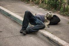 Betrunkene Person, die draußen liegt Lizenzfreie Stockfotos