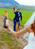 Betrunkener Bräutigam auf einem Fahrrad, das einen Hochzeitsblumenstrauß hält, läuft eine Braut mit einer Bierflasche nach Stockfotos