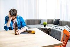 Betrunkener männlicher Alkoholiker mit Getränken zu Hause lizenzfreie stockfotos