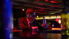 Betrunkener Mann allein bleibt spät in der Bar, beendet die Whiskyflasche und erleidet Krise stock footage