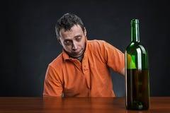 Betrunkener Mann betrachtet die Flasche Lizenzfreie Stockfotos