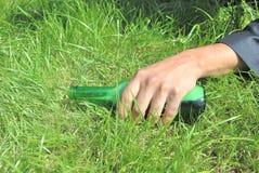 Betrunkener Mann, der auf Rasen mit Flasche liegt Stockbilder
