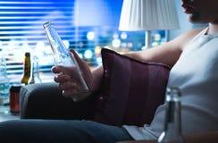 Betrunkener Mann, der auf Sofa sitzt und eine Flasche Alkohol hält Lizenzfreies Stockbild