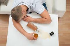 Betrunkener Mann, der auf Tabelle mit Alkohol schläft Lizenzfreies Stockbild