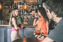 Betrunkener Mann, der an der Bar, trinkendes Cocktail, Mädchen betrachtend sitzt stockfotografie