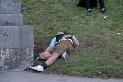 Betrunkener Mann, der in dem Bayern, Oktoberfest, München schläft lizenzfreie stockfotografie