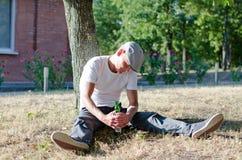 Betrunkener Mann, der eine Flasche Alkohol erfasst Stockbild