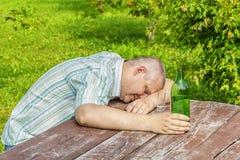 Betrunkener Mann, der nahe Flasche Alkohol auf Tabelle schläft Lizenzfreie Stockfotos