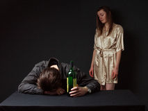 Betrunkener Mann schläft auf dem Tisch mit der Flasche in der Hand, Lizenzfreie Stockfotos