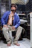 Betrunkener Mann sitzt in einer Toilette mit einer Flasche Whisky Lizenzfreie Stockfotografie