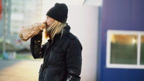 Betrunkener obdachloser Mann mit Getränkalkohol von der Papiertüte bei der Stellung an der Stadtstraße Stockfoto