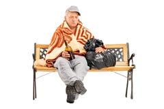 Betrunkener obdachloser reifer Mann, der auf einer Bank mit Flasche sitzt Stockbilder