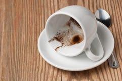 Betrunkener Tasse Kaffee mit Kaffeesatz auf Untertasse auf Holztisch, niedrige Winkelsicht mit Platz für Text Lizenzfreie Stockbilder