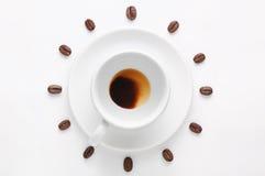 Betrunkener Tasse Kaffee und Kaffeebohnen gegen den weißen Hintergrund, der die Uhrskala angesehen von der Spitze bildet Lizenzfreie Stockfotos
