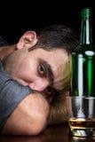 Betrunkener und deprimierter Mann, der allein trinkt Lizenzfreie Stockfotos