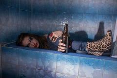 Betrunkenes Mädchen, das in einer Badewanne mit einer Flasche in ihrer Hand liegt Lizenzfreies Stockfoto