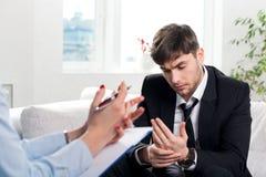 Betryckt man som talar med psykologen Royaltyfri Foto