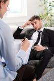 Betryckt man som talar med psykologen Royaltyfria Bilder