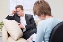 Deprimerad man som talar med psykologen Fotografering för Bildbyråer