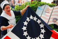 Betsy Ross Reenactor, Philadelphia. A Betsy Ross impersonator unfolds a Colonial American Flag, and talks of the symbolism of the stars and stripes Stock Photo