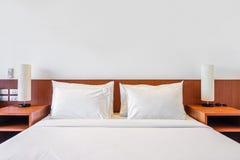 Bett, Kissen und Lampe Stockbilder