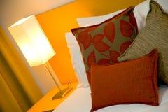 Bett, Kissen und Lampe Stockbild