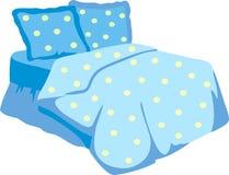 Bett mit blauer Decke und Kissen stockbild
