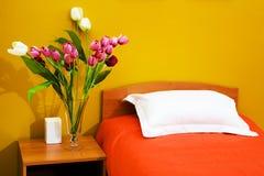 Bett mit einer orange Bettdecke Stockfoto