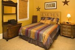 Bett mit gestreifter Bettdecke im reichlichen Haus Lizenzfreies Stockfoto
