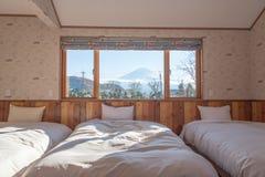 Bett mit M.Ü. Fuji-Ansicht als Hintergrund außerhalb des Fensters Lizenzfreie Stockbilder