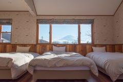 Bett mit M.Ü. Fuji-Ansicht als Hintergrund außerhalb des Fensters Lizenzfreie Stockfotografie