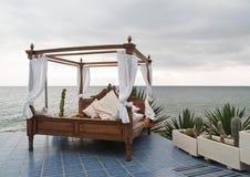 Bett mit vier Plakaten durch das Meer Stockfotografie
