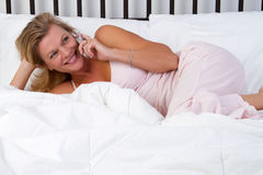 Bett-Telefon-Frau Lizenzfreie Stockfotografie
