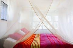 Bett unter einem Moskitonetz lizenzfreie stockfotos