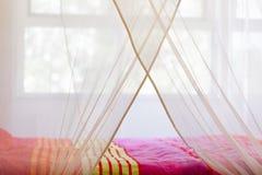 Bett unter einem Moskitonetz stockfotografie
