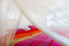 Bett unter einem Moskitonetz lizenzfreie stockbilder