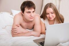 Betten Sie die Paare, die auf Laptop-Computer im Schlafzimmer glücklich sind Stockbilder
