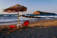 Betten und Regenschirme auf dem Strand Stockfotografie