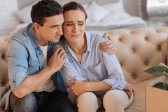 Kind calm man supporting and hugging his sad wife. Better. Attentive kind loving men sitting on the sofa and hugging his sad unhappy dismissed wife while trying royalty free stock photo