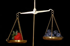 The Better Fruit. An old-fashioned balance scale with a strawberry on one side and blueberries on the other Royalty Free Stock Photo